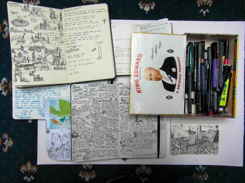 A lot of gibberish. Top book is the sketchbook I used when doing radio interviews, as you can see I often let my mind wander. My stationary box is an old cigar case that I used to keep watches and clockwork stuff in. My favourite pens to use are Staedtler .3 &.005s, mainly a holdover from when I used to do a lot of technical & graph comm drawing. They probably aren't the best writing or artist pens, but I love them. You can see an example of the cityscapes in my wee moleskine below it.