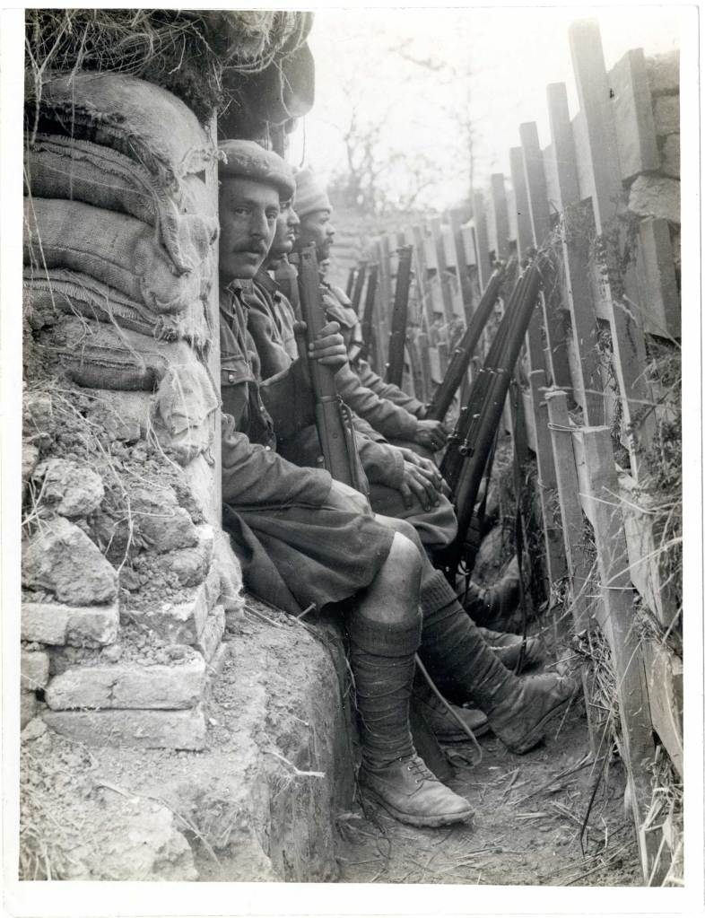 Highlanders and Indian Dogras sitting in a trench, 1915.